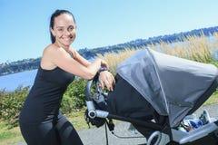 Jonge moederjogging met een kinderwagen Stock Afbeeldingen