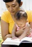 Jonge moederlezing terwijl baby-sitting Royalty-vrije Stock Foto