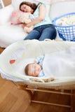 Jonge moederslaap op de bank met haar baby stock afbeelding