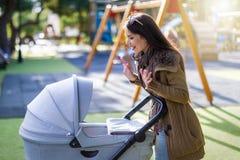 Jonge moederspelen met haar pasgeboren baby in het park stock foto