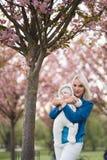 Jonge moedervrouw die van vrije tijd met haar kind genieten van de babyjongen - Kaukasisch wit kind met zichtbare de hand van een royalty-vrije stock afbeelding