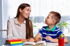 Jonge moederzitting bij een lijst die thuis haar kleine zoon met zijn thuiswerk van school helpen aangezien hij nota's in een not Stock Afbeeldingen