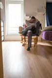 Jonge moederzitting en het rusten in een schommelstoel die haar houden Stock Afbeeldingen