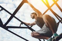 Jonge moedige mens die en bij de hoge metaalbouw beklimmen zitten stock fotografie