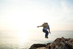 Jonge moedige reiziger die met rugzak over de rotsen springen stock fotografie