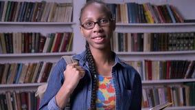 Jonge mooie Afrikaanse Amerikaanse vrouw in glazen die boek in bibliotheek lezen en camera bekijken, gelukkig, het glimlachen stock videobeelden