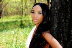 Jonge Mooie Afrikaanse Vrouw die tegen een Boom leunen royalty-vrije stock afbeelding