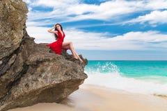 Jonge mooie alleen vrouw in rode kledingszitting op de rots  Royalty-vrije Stock Foto's