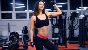 Jonge mooie atletenvrouw in gymnastiek die haar spieren tonen stock videobeelden