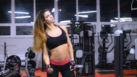 Jonge mooie atletenvrouw in gymnastiek die haar spieren tonen stock video
