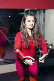 Jonge mooie atletische meisjestreinen op de simulator in de gymnastiek sportieve vrouw in rode beenkappen die oefening doen stock foto