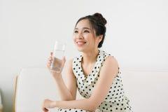 Jonge mooie Aziatische vrouw die een glas water houden terwijl sitti stock foto