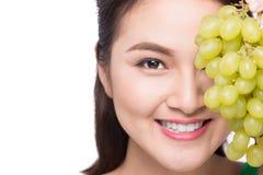 Jonge mooie Aziatische vrouw die verse die druiven eten op whit worden geïsoleerd Stock Foto