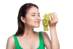 Jonge mooie Aziatische vrouw die verse druiven op whit eten Stock Afbeelding