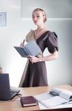 Jonge mooie bedrijfsvrouw aan het werk met boek Stock Afbeeldingen