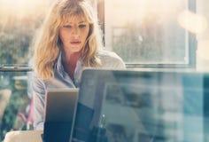 Jonge mooie bedrijfsvrouw die bij laptop computer op zonnig kantoor werken Panoramische vensters op vage achtergrond Stock Afbeelding