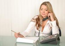 Jonge mooie bedrijfsvrouw die, die telefoon houdt en nota's leest Royalty-vrije Stock Foto's