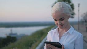 Jonge Mooie Bedrijfsvrouw die Tabletpc in openlucht op de Zonsondergang met behulp van stock foto's