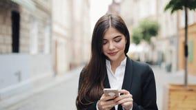 Jonge mooie bedrijfsvrouw gebruikend smartphone en lopend op de oude straat Zij die Internet surfen Concept: nieuw