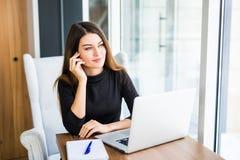 Jonge mooie bedrijfsvrouw met notitieboekje in het heldere moderne bureau Stock Fotografie