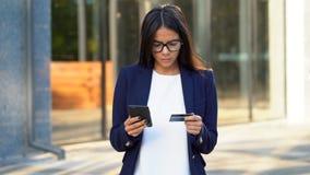 Jonge mooie bedrijfsvrouw of student die bankwezen met haar smartphone op de bureaubouw achtergrond gebruiken Online stock videobeelden