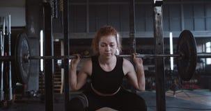 Jonge, mooie blanke, rode, harige atletische vrouw die zware barbel optilt terwijl ze in de grote professionele gyroscoop trage b stock footage