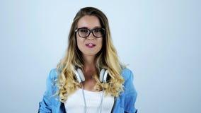 Jonge mooie blonde grappige vrouw die in oogglazen kauwgom met hoofdtelefoons op haar hals op geïsoleerde witte achtergrond opbla stock video