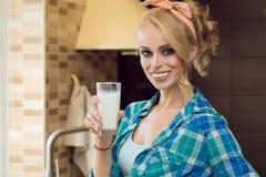 Jonge mooie blonde huisvrouw in de keuken die een glas melk en het glimlachen houden stock foto's