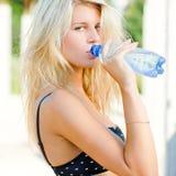 Jonge mooie blonde vrouw in bustehouder drinkwater Royalty-vrije Stock Foto's