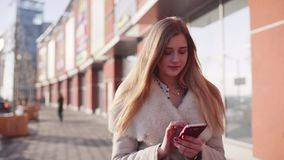Jonge mooie blondedame die onderaan de eenzame straat in het stadscentrum lopen, die haar smartphone voor mededeling gebruiken stock footage
