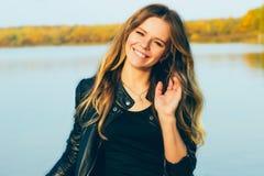 Jonge mooie blondevrouw in de herfstpark met meer in donkere de glimlach perfecte tanden van het leerjasje tijdens zonsondergang Royalty-vrije Stock Foto's