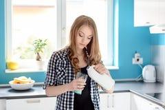 Jonge mooie blondevrouw die een melk gieten Royalty-vrije Stock Fotografie