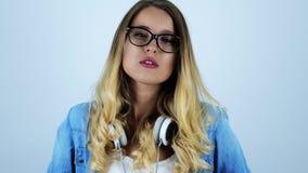 Jonge mooie blondevrouw in oogglazen kauwgom met hoofdtelefoons op haar hals op geïsoleerde witte achtergrond stock videobeelden