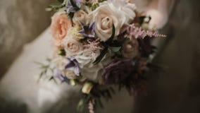 Jonge mooie bruid die het huwelijksboeket houden Close-upmening van wijfje met bloemen vóór ceremonie stock videobeelden
