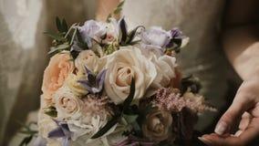 Jonge mooie bruid die het huwelijksboeket houden Close-upmening van wijfje wat betreft de bloemen vóór ceremonie stock videobeelden