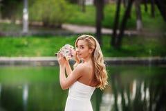 Jonge mooie bruid in een witte kleding met een boeket status Stock Foto's