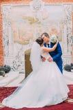 Jonge mooie bruid en bruidegom in luxe uitstekende binnenlandse ruimte op hun huwelijk royalty-vrije stock foto