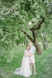 Jonge mooie bruid in huwelijkskleding met knappe bruidegom in openlucht Stock Fotografie