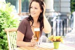 Jonge mooie brunette met een bierglas royalty-vrije stock afbeelding