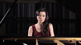 Jonge mooie dame die de piano spelen, die voor de camera stellen stock videobeelden