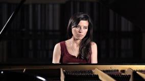 Jonge mooie dame die de piano spelen, die voor de camera stellen stock video