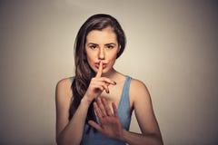 Jonge mooie die vrouw met vinger op lippen op grijze muurachtergrond wordt geïsoleerd royalty-vrije stock afbeelding