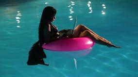 Jonge mooie donkerbruine vrouw die aan laptop in de pool werken stock video