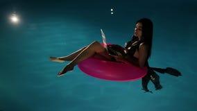 Jonge mooie donkerbruine vrouw die aan laptop in de pool werken stock videobeelden