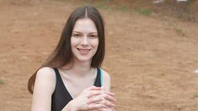 Jonge mooie donkerbruine vrouw die de camera en het glimlachen zitting op het strand in een zwempak bekijken stock video