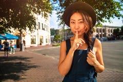 Jonge mooie donkerbruine vrouw die stilteteken met vinger op lippen in openlucht tonen royalty-vrije stock foto's