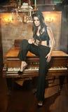 Jonge mooie donkerbruine vrouw die in zwarte mannelijke broeken, hoed en steunen op een piano in uitstekend landschap zitten Roma Stock Foto