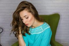 Jonge mooie donkerbruine vrouw in een turkooise blouse stock afbeeldingen