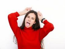 Jonge mooie donkerbruine vrouw in rode sweater die hoornen met haar vingers tonen die tegen witte achtergrond stellen royalty-vrije stock fotografie