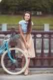 Jonge mooie, elegant geklede vrouw met fiets Stock Afbeelding